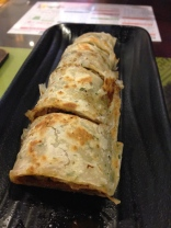 """""""Beef roll"""" (beef, cucumber, spring onion, and a delicious sauce wrapped in an onion tortilla)."""